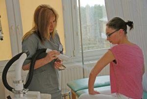 terapeuta ubrany w szare ubranie medyczne ochronne wykonuję zabieg rehabilitacyjny pacjentce ubranej w kolorze różowym na łóżku medycznym koloru zielonego aparatem koloru białego