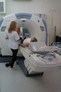 pracownik tk ubrany w ubranie ochronne medyczne koloru białego wykonuje badanie tomografem pacjentowi w pracowni TK