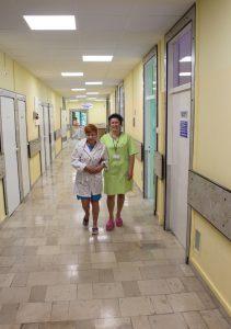 korytarz oddziału szpitala koloru żółtego z szarą podłogą uśmiechają się dwie osoby ubrane w odzież ochronną koloru zielonego i białego