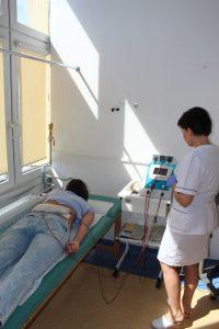 terapeuta ubrany w białe ubranie medyczne ochronne wykonuję zabieg rehabilitacyjny pacjętowi na łóżku medycznym koloru zielonego aparatem koloru białego