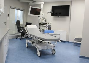 w pokoju badań endoskopowych znajduje się łóżko medyczne koloru szarego, stołek obrotowy koloru niebieskiego, na scianie ekran koloru czarnego wraz z aparaturą do badań endoskopowych i fotel obrotowy koloru czarnego.