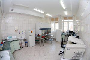 pokój laboratorium koloru białego w którym znajdują się urzadzenia koloru białego wraz biurkiem na którym znajduje się zestwa komputerowy do drukowania wyników badań