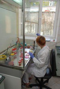 pracownik laboratorium wykonujący badania laboratoryjne w pokoju z oszklonym aparatem laboratoryjnym w którym znajdują się próbki z badaniami pacjentów szpitala