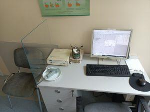 na biurku koloru białego znajduję się spirometr koloru szarego wraz z komputerem z białym monitorem i czarna klawiaturą i myszką komputerową w Dziale Badań Czynnościowych Układu Oddechowego