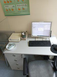 na biurku koloru białego znajduję się spirometr koloru szarego wraz z komputerem z białym monitorem i czarna klawiaturą w Dziale Badań Czynnościowych Układu Oddechowego