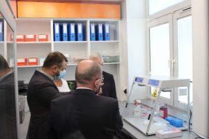 Osoby ubrane w ubrania wizytowe z maseczkami ochronnymi na twarzy w pomieszczeniu PCR w którym znajduje sie regał z kolorowymi segregatorami oraz aparat do badań PCR koloru białego oszklony.