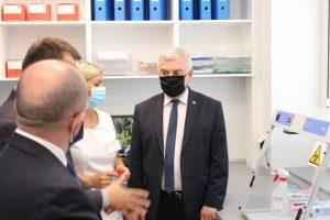 Osoby ubrane w ubrania wizytowe i maseczki ochronne w pokoju Pracowni PCR