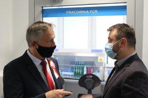 Osoby ubrane w ubrania wizytowe i maseczki ochronne na twarzy przy drzwiach Pracowni PCR.