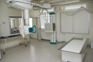 pracownia rtg wraz z aparatem do badaniań koloru białego i białym stołem do diagnostyki RTG oraz drzwiami koloru białego