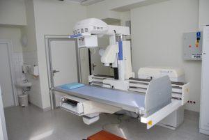 pracownia rtg wraz z aparatem do badaniań koloru białego i niebieskim łóżkiem do diagnostyki RTG oraz drzwiami koloru białego