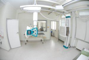 pracownia rtg wraz z aparatem do badaniań koloru białego i szarym łóżkiem do diagnostyki RTG oraz drzwiami koloru białego