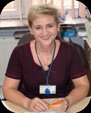 Kobieta ubrana w ubranie ochronne koloru fioletowego uśmiecha się