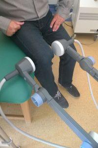 osoba ubrana w czarne spodnie i czarne obuwie podczas zabiegu rehabilitacyjnego na łóżku medycznym zielonym