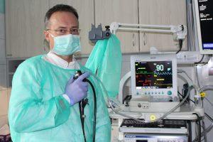 lekarz ubrany w niebieskie ubranie ochronne oraz niebieską meseczką ochronna na twarzy trzymający w ręce na której znajduję się rękawiczka lateksowa aparat do gastroskopii koloru czarnego