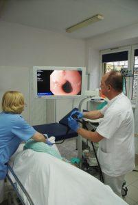 lekarz wykonujący badaniie gastroskopii ubrany w białą odzież ochronną w ręku trzyma aparat do badania koloru czarnego wraz z pielęgniarka ubraną w niebieskie ubranie ochronne pacjentowi szpitala i spogląda na monitor koloru białego