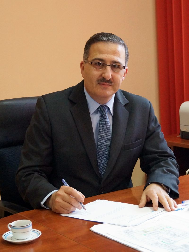 Dyrektor Szpitala Youssef Sleiman ubrany w ubranie wizytowe garnitur koloru granatowego w biurze przy biurku koloru brązowego podpisuje dokumenty