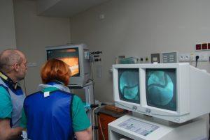 dwie osoby w ubranich koloru niebieskiego podczas operacji ogląda wykonywaną operację na trzech monitorach aparatu endoskopowego koloru białego