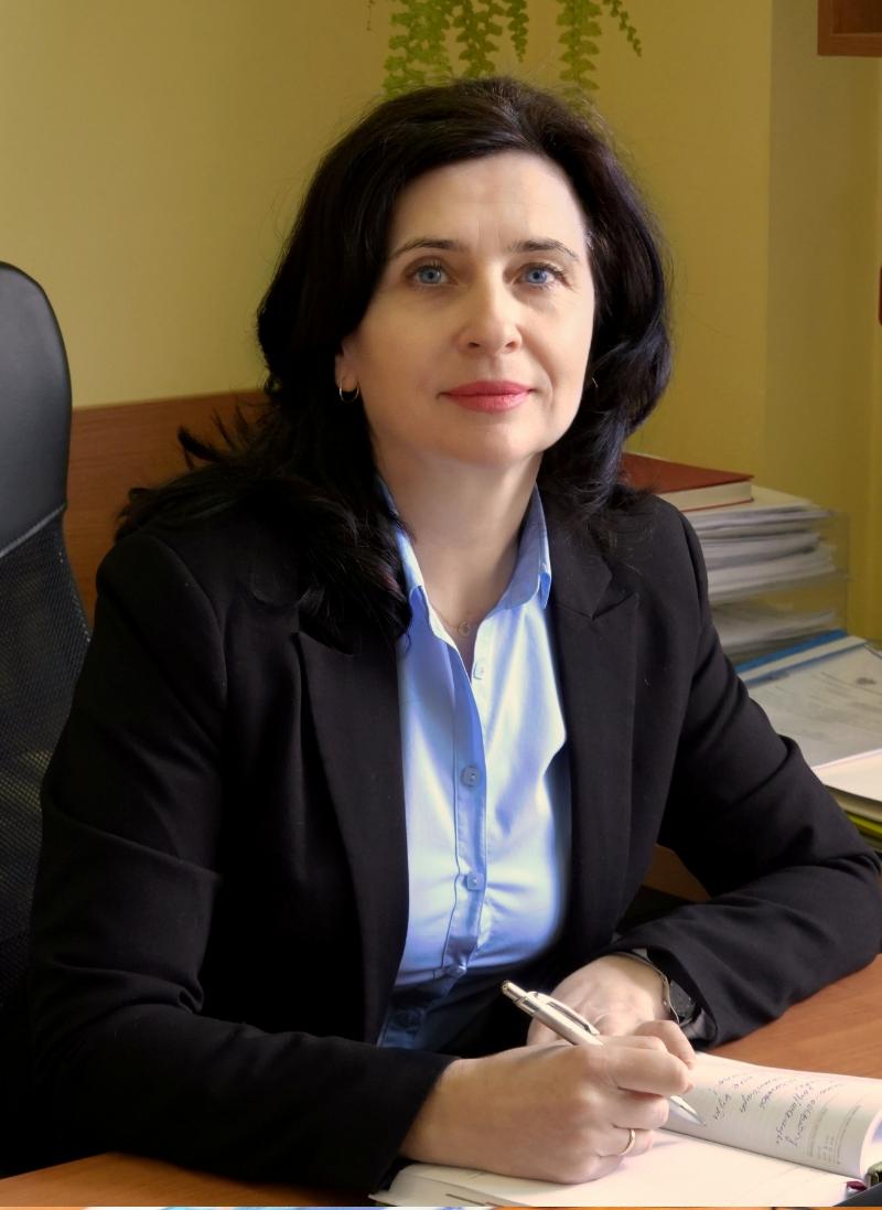 Zastępca Dyrektora ds. Planów i Finansów ubrana w ubranie wizytowe w biurze przy biurku koloru brązowego z dokumentami