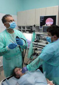 lekarz ubrany w niebieskie ubranie ochronne oraz niebieską meseczką ochronna na twarzy wykonujący badaniie gastroskopii wraz z pielęgniarka pacjentowi szpitala ogląda wynik badania na monitorze koloru szarego