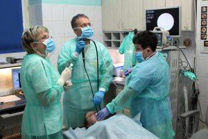lekarz ubrany w niebieskie ubranie ochronne oraz niebieską meseczką ochronna na twarzy wykonujący badaniie gastroskopii wraz z pielęgniarka pacjentowi szpitala w pokoju koloru białego