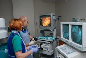 dwie osoby w ubranich koloru niebieskiego podczas operacji ogląda wykonywaną operację na trzech monitorach aparatu endoskopowego