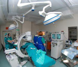 cztery osoby w ubraniach koloru niebieskiego wykonujące zabieg na bloku operacyjnym obserwują przebieg operacji na trzech monitorach koloru szarego