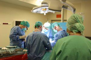 czterech lekarzy ubranych w ubrania ochronne oraz maseczki ochronne wykojuja zabieg chirurgiczny na bloku operacyjnym w asyscie instrumentariuszki przygotowujących narzedzia do operacji na zielonym stole operacyjnym