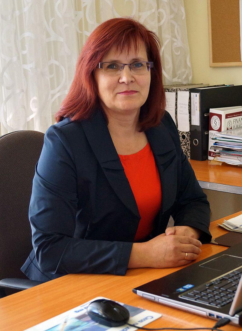 główna księgowa ubrana w ubranie wizytowe w biurze przy biurku koloru brązowego z laptopem koloru czarnego