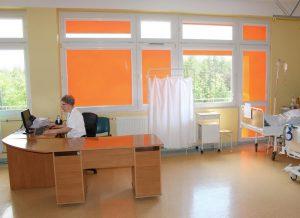 Sala chorych. W oknie pomarańczowe rolety. Pielęgniarka wprowadza dane pacjentów do komputera.