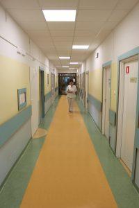korytatarz oddziału szpitala koloru zółto zielonego i białym drzwiami idzie osoba ubrana w odzież białą ochronną