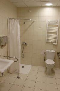 łazienka koloru białego w której znajduję się umywalka z baterią koloru białego wraz z podajnikiem papieru w kolorze srebnym z prysznicem z białym parawanem oraz kompakt WC koloru białego