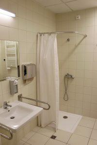 łazienka koloru białego w której znajduję się umywalka z baterią koloru białego wraz z podajnikiem mydła i papieru w kolorze srebnym z prysznicem z białym parawanem