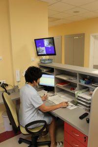 osoba w pokoju koloru żółtego ubrana w odzież ochronną medyczna siedzi na fotelu obrotowym koloru czarnego przy biurku na którym znajduje się telefeon koloru cxarnego oraz monitor kompuyterowy przegląda dokumentację medyczną