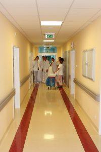 korytarz oddziału szpitala koloru zółtego na podłodze pasy koloru czerwonego znajduja się osoby ubrane w biała odzież ochronną prowadzą rozmowę obok na kólkach wóżek medyczny obrotowy koloru białego