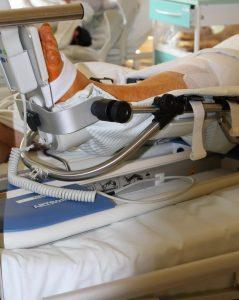 stopa ludzka po zabiegu operacyjnym ortopedycznym w szynie usztywniającej koloru srebno czarnego