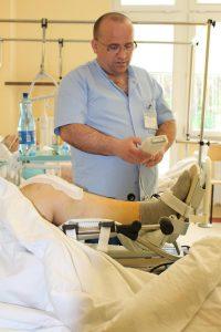 lekarz ortopeda na sali chorych ubraby w odzież ochronną kolou niebieskiego przy łóżku pacjęta po operacji kolana trzyma w ręku wyciąg mechaniczny koloru białego