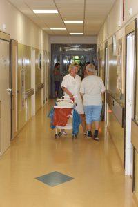 korytarz oddziału szpitala koloru żółtego diwe osoby ubrane w białąodzież ochronną , jedna z nich prowadzi biały wóżek medyczny obrotowy