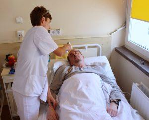 sala oddziału szpitala pielęgniarka ubrana w białą odzież ochronną mierzy temperaturę pacjentowi ubranemu w piżamę koloru szarego leżącego na łóżku z białą pościelą obok znajduję się okno z żółtą rolętą