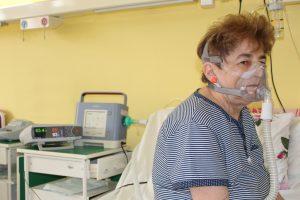 Pacjentka oddziału szpitala w masce tlenowej na twarzy siedzi nałóżku medycznym. obok aparat do podawania tlenu koncentrator tlenu.