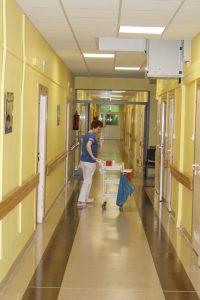 Korytarz oddziału koloru żóltego pielęgniarka ubrana w odzież ochronną z wózkiem medycznym
