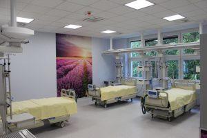 na sali oddziału OAIT koloru fioletowego znajduję się na ścianie fototapeta koloru fioletowego z zachodem słońca oraz trzy łóżka medyczne koloru biało żółtego wraz z aparaturą do ratowania życia ludzkiego