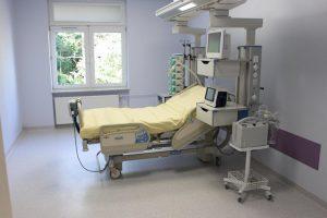 w pokoju koloru filetowego znajduję się łóżko medyczne koloru biało żółtego wyposażonę w aparaturę koloru białego do ratowania ludzkiego życia