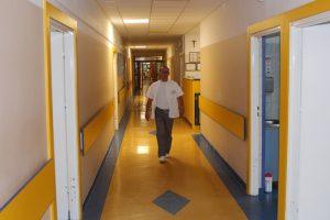 Lekarz idący żółtym korytarzem na wizytę do pacjenta.