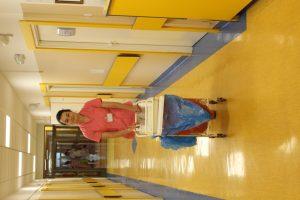 Uśmiechnięta pielęgniarka w różowym ubraniu ochronnym, idąca przez korytarz z wózkiem.
