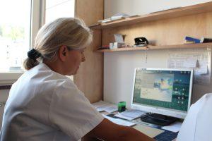 Pielęgniarka, ubrana w biały fartuch ochronny, wprowadza dane do internetowej bazy pacjentów.