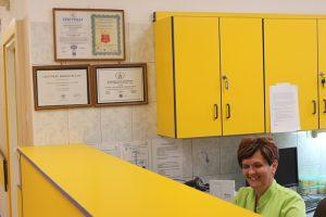 Dyżurka pielęgniarek, wyposażona w żółte meble. Uśmiechnięta pielęgniarka w zielonym ubraniu ochronnym, pełniąca dyżur.