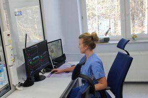 w pokoju koloru niebieskiego osoba ubrana w odzież ochronna koloru niebieskiego siedzi na fotelu obrotowym koloru niebieskiego spogląda na monitory koloru czarnego znajdujące się na biurku koloru szarego