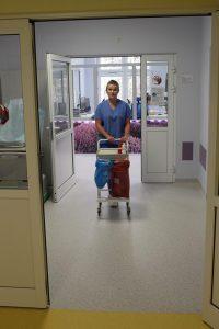 osoba stojąca w drzwiach koloru białego ubrana w ubranie ochronne medyczne koloru niebieskiego trzyma w rękach wózek medyczny koloru białego na kółkach na oddziałe OAiT