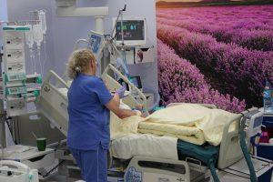 sala oddziału OAIT pielęgniarka ubrana w niebieska odzież ochronna przy pacjęcie leżącym na łóżku medycznym podpiętym do aparatury wspomagającej oddychanie obok widoczna na ścianie fototapeta koloru fioletowego