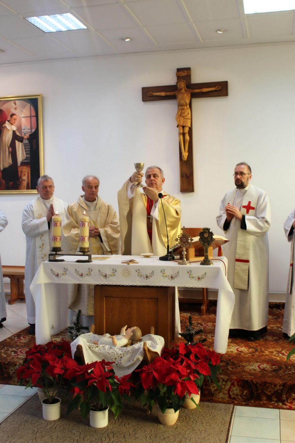 czterech księży ubranych w białe ubrania podczas mszy świętej w kaplicy szpitalnej